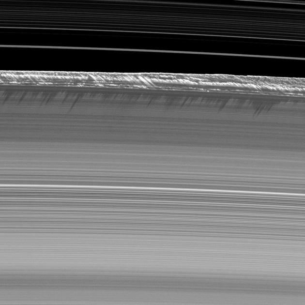 Cet extraordinaire gros-plan sur les anneaux de Saturne a été obtenu par la sonde Cassini. Le champ mesure 1200 km de large. En avant-plan, la zone de l'anneau B de Saturne. En arrière-plan, en haut de l'image, la zone beaucoup moins dense de la division de Cassini. En bordure de l'anneau apparaissent de véritables vagues de glace, hautes de 2500 mètres, levées par les perturbations gravitationnelles de petits satellites circulant dans les anneaux. Ces structures irréelles, éclairées par un Soleil rasant, projettent leurs ombres sur l'anneau B. Photo JPL/Nasa.