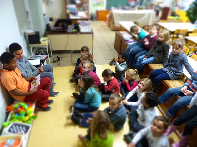 Des élèves de CM2 lisent devant une classe de CP / Ph. Jyaire via Flickr - CC BY 2.0