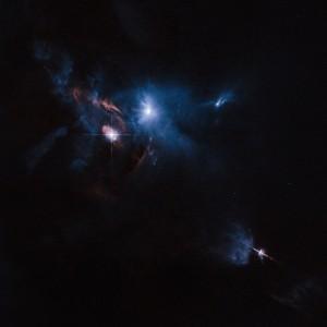 HL Tauri, en haut de l'image, appartient à un groupe d'étoiles en formation, voilées dans un immense nuage de gaz et de poussière interstellaire, dans la constellation du Taureau. En bas et à droite de l'image, apparaît une autre étoile naissante, V1213 Tauri. Photo Nasa/ESA/STSCI.
