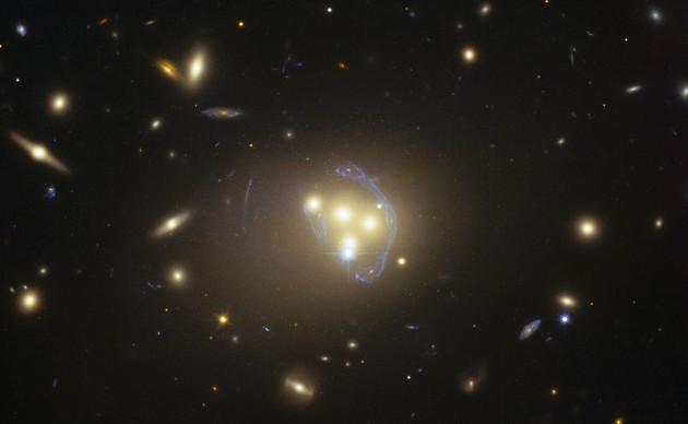 L'amas de galaxies Abell 3827 se trouve à près de 1,4 milliard d'années-lumière de la Terre. Au cœur de cet amas, quatre galaxies elliptiques géantes sont lancées dans un processus de fusion. Leur masse énorme – plusieurs milliers de milliards de masses solaires – courbe l'espace-temps autour d'elles et forme une lentille gravitationnelle, laquelle dessine un spectaculaire mirage gravitationnel – les arcs bleutés qui auréolent les galaxies - c'est à dire l'image déformée et agrandie d'une galaxie lointaine située à l'arrière plan...Photo Nasa/ESA/STSCI.