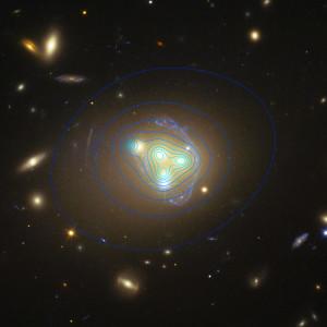 La carte de la matière noire du cœur de l'amas Abell 3827, superposée à sa photographie, prise par le télescope spatial Hubble. Le halo de matière noire de la galaxie N 1, à gauche, est décalée de 5000 années-lumière par rapport à la matière visible de la galaxie... Photo Nasa/ESA/STSCI.