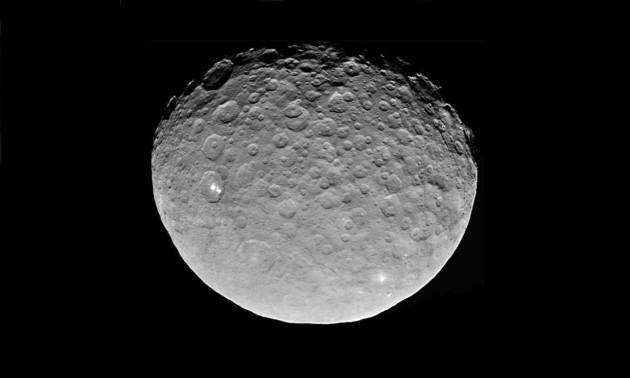La planète naine Cérès, vue par la sonde américaine Dawn le 6 mai 2015. Satellisée à moins de 14 000 kilomètres de la surface du petit astre, Dawn montre ici des détails de l'ordre de 1400 mètres seulement. A gauche de l'image, les spots blancs qui intriguent tant les astronomes. Photo JPL/Nasa.