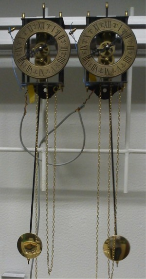 Photo of the experimental setup. The clocks can be seen hanging from the Al rail. The weights are outside of the picture. The cables in the background connect the optical sensors.