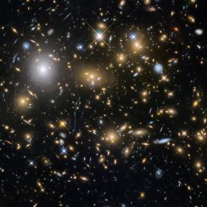 MACS J0717,5+3745, situé dans la constellation du Cocher, à environ 5 milliards d'années-lumière de la Voie lactée, est l'un des plus grands amas de galaxies connus dans l'Univers. Dans ce véritable océan de galaxies se pressent des millions de milliards d'étoiles. C'est en arrière-plan de cet amas, qui joue aussi le rôle de lentille gravitationnelle, que les astronomes ont découvert les plus lointaines galaxies de l'Univers. Photo Nasa/ESA/STSCI.