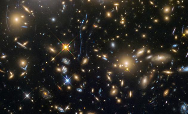 Au cœur de l'amas de galaxies MACS J0717,5+3745, situé à environ 5 milliards d'années-lumière de la Voie lactée... La masse invraisemblable de cette formidable agglomération cosmique courbe l'espace-temps autour d'elle et agit comme une immense lentille naturelle. Cette lentille gravitationnelle permet de de voir des galaxies situées en arrière-plan. Déformées, agrandies, amplifiées, sur cette image, elles apparaissent comme de grandes virgules fantomatiques et bleutées. Photo Nasa/ESA/STSCI.